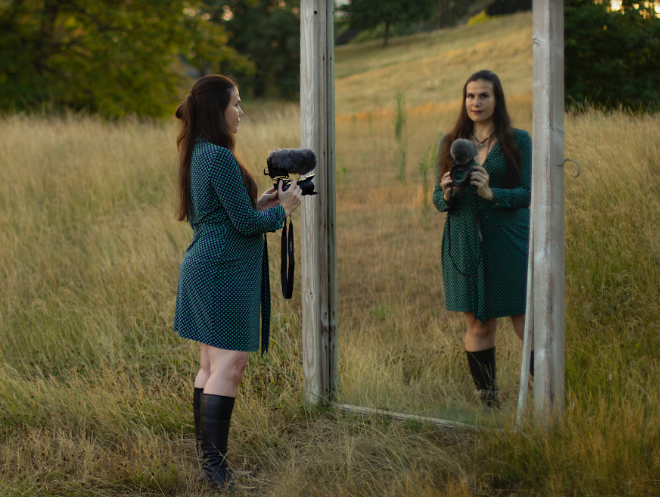 Hidalgo stands before a large mirror in a field with her video camera. As she looks into the mirror, we see her reflection looking back at us.